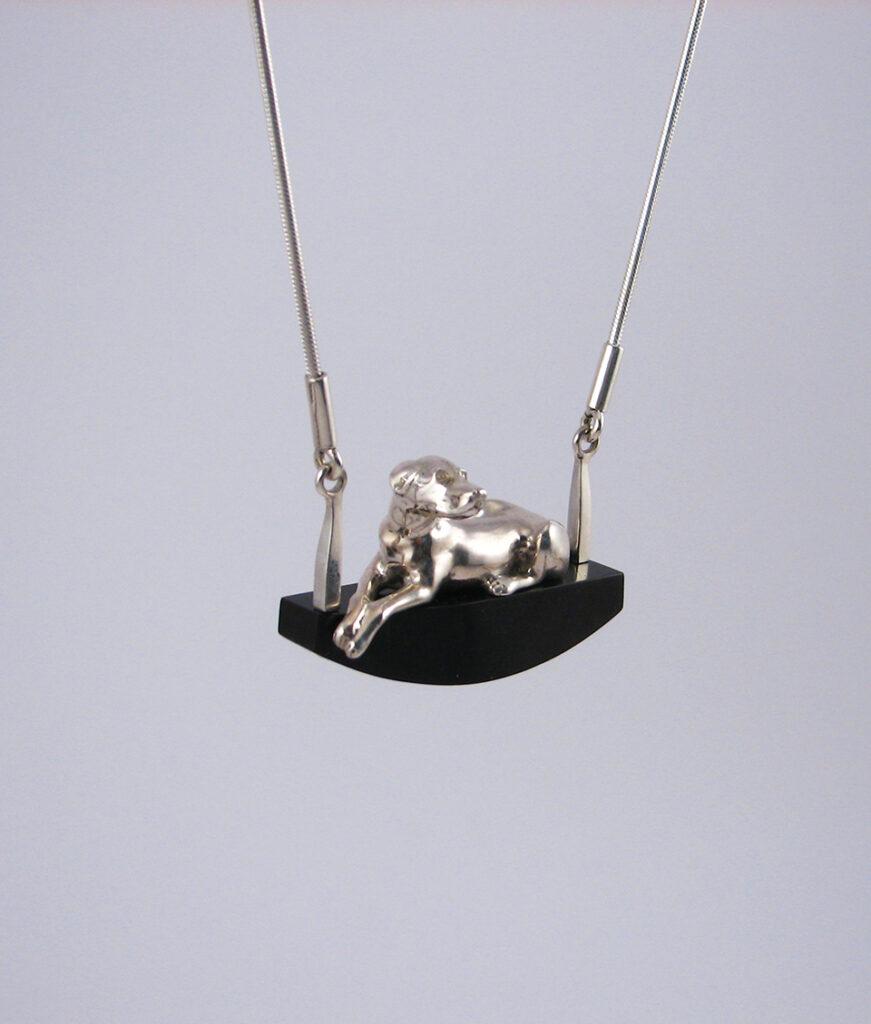 Ezüst kutya fekszik / ül egy fekete posztamensen kígyó láncon