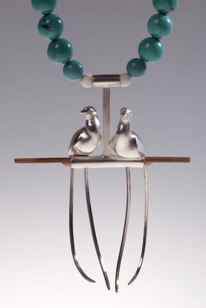 Lantok nyaklánc - két kecses madár ül egymás mellett egy T alakú ágon