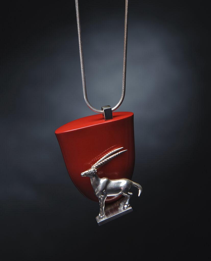 Vörös háttér előtt oryx gazellát ábrázoló ezüst függő